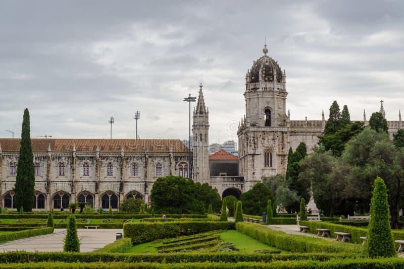 La vista de la iglesia de Santa Maria del monasterio de Jeronimos a través del jardín hermoso en el cuadrado del imperio, Lisboa  fotos de archivo