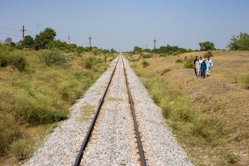 La vista de la línea ferroviaria de Paquistán en Peshawar y la gente funcionan con una manera fotos de archivo