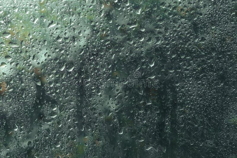 La vista de las gotas de lluvia en ventana con el árbol verde, rojo y amarillo del color en el fondo Autumn Abstract empañó el co foto de archivo