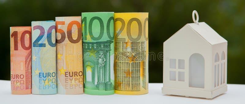 La vista de la pila de la moneda con el modelo de la casa en el fondo verde, ahorros planea para contener, concepto financiero, h imagen de archivo libre de regalías