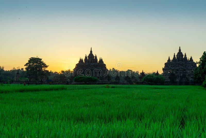 La vista de la salida del sol en un pueblo con un fondo plaosan del templo budista en Yogyakarta, Indonesia imagen de archivo libre de regalías