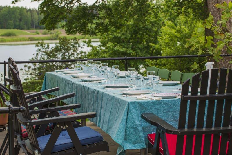 La vista de la tabla al aire libre del partido cubierta con el mantel del verde de mar listo sirvió Naturaleza hermosa alrededor foto de archivo libre de regalías