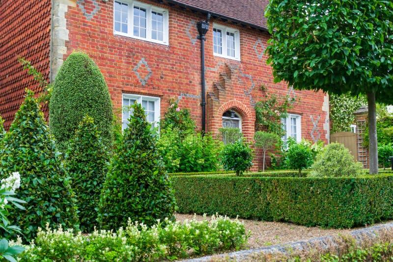 La vista de un exterior hermoso de la casa con el jardín y la puerta principal en Inglaterra foto de archivo
