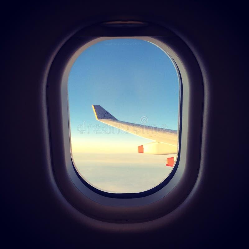 La vista del ala hacia fuera acepilla la ventana, puesta del sol imagenes de archivo