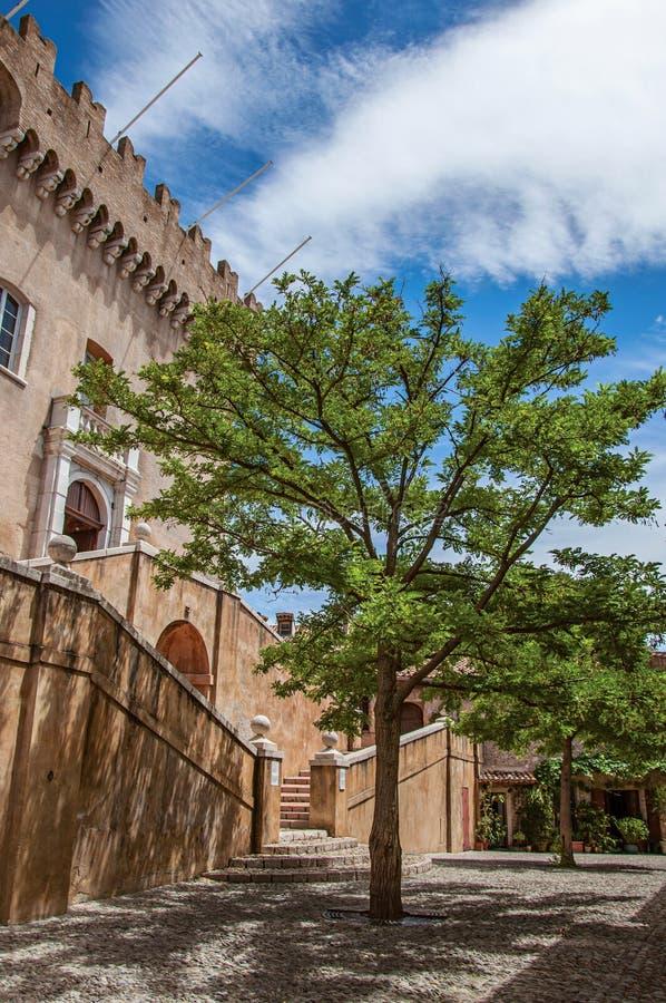 La vista del callejón con los árboles y la fachada del Grimaldi se escudan en el Haut-de-Cagnes foto de archivo