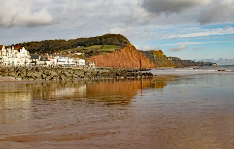 La vista del easten l'estremità del lungomare di Sidmouth e della scogliera dell'arenaria Questa scogliera ha rockfalls regolari  fotografie stock