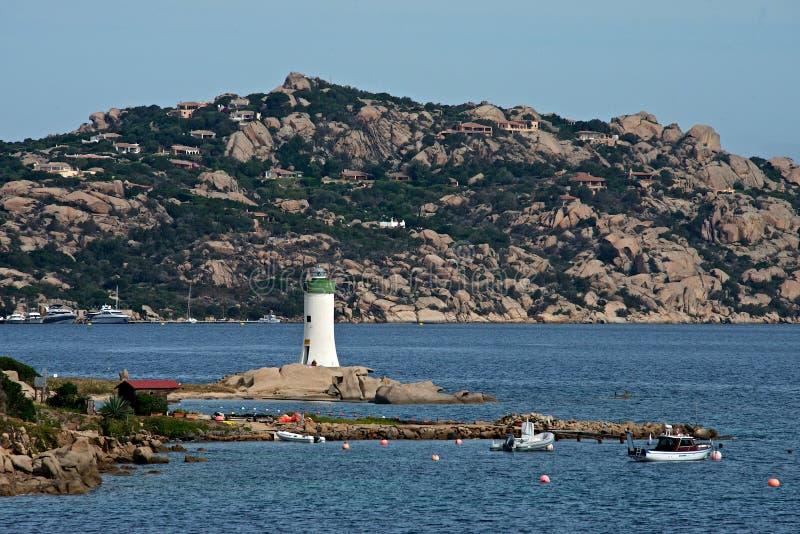 La vista del faro de Palau con los barcos amarró en el mar azul de Cerdeña foto de archivo
