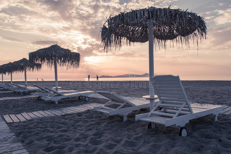 La vista del mare e della spiaggia con i parasoli a colore del chillout del tramonto ha spaccato la tonalità fotografia stock
