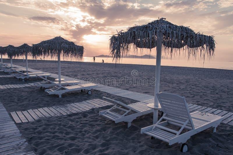 La vista del mare e della spiaggia con i parasoli a colore del chillout del tramonto ha spaccato la tonalità fotografia stock libera da diritti