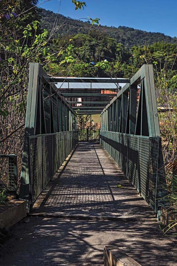 La vista del puente del hierro sobre el pequeño río en Monte Alegre hace Sul imágenes de archivo libres de regalías
