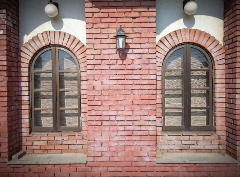 La vista delantera de dos que el vintage redonde? la ventana en ladrillo rojo resistido bloquea el fondo de la pared foto de archivo