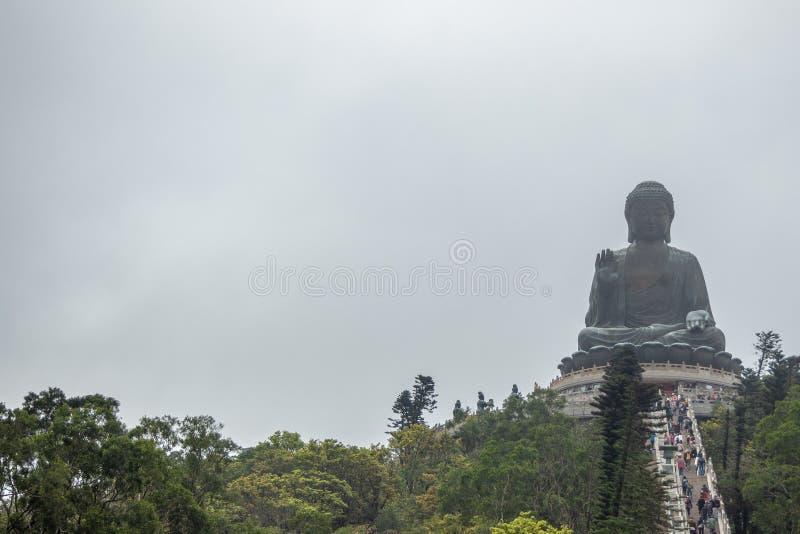 La vista delantera de Tian broncea al gran Buda en fondo cubierto del cielo fotografía de archivo