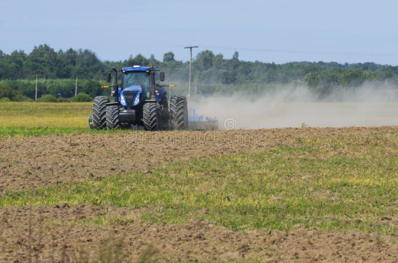 La vista delantera del tractor ara el campo con polvo que remolina foto de archivo
