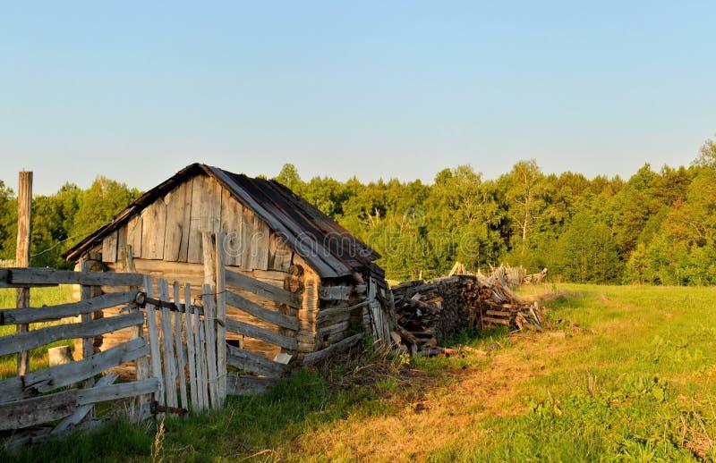 La vista dell'estate di vecchio bagno di legno e recinta i raggi del tramonto fotografia stock