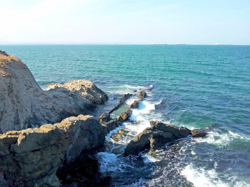La vista della spuma rocciosa della costa colpisce le rocce Giorno pieno di sole di estate fotografie stock