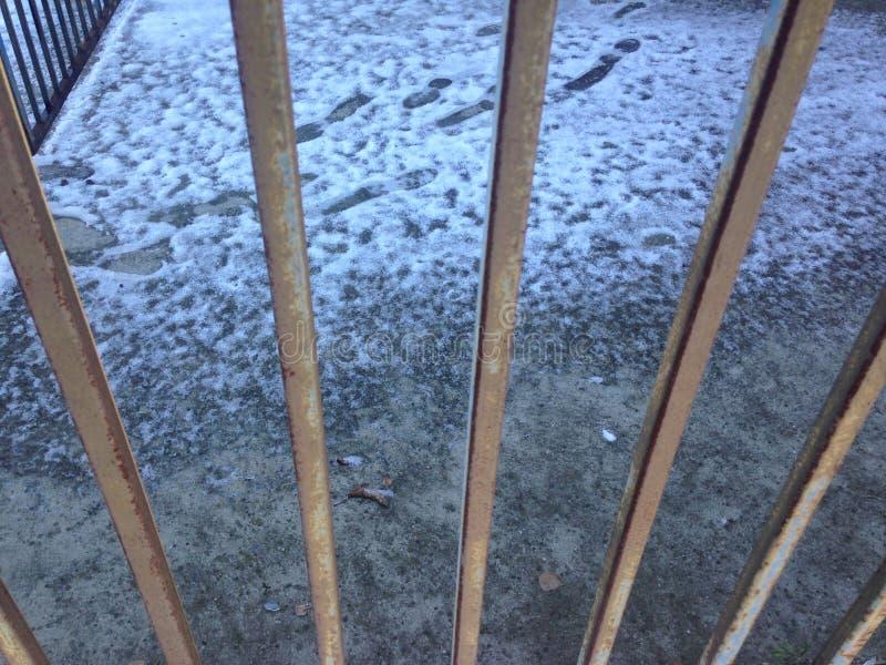 La vista delle orme sulla neve tramite il recinto fotografia stock