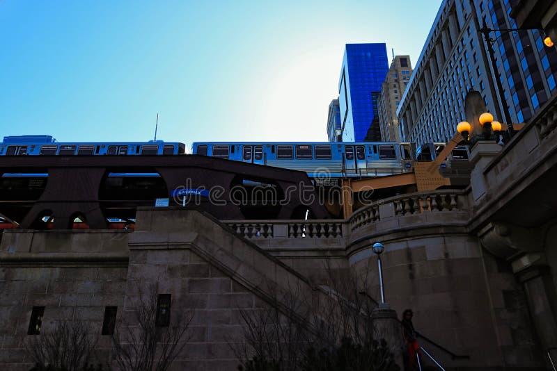 La vista di angolo basso di Chicago ha elevato il treno del ` di EL del ` sopra la via di pozzi con le scale che conducono giù al fotografia stock
