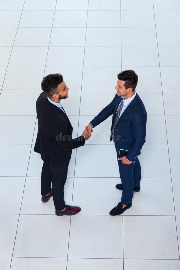 La vista di angolo superiore di gesto di benvenuto di scossa della mano degli uomini d'affari, due uomini di affari fa l'affare l immagini stock