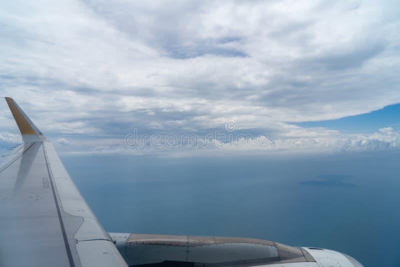 La vista di bello cloudscape bianco con le tonalità del fondo dell'oceano profondo e del cielo blu dal volo spiana la finestra co fotografia stock libera da diritti