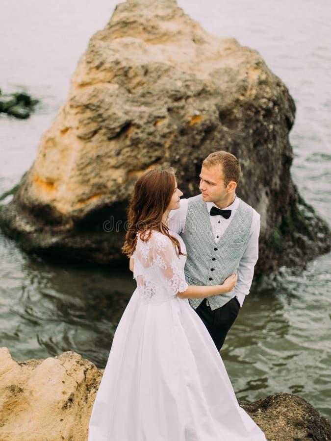 La vista di cui sopra del delle persone appena sposate sorridenti che abbracciano mentre stando sulla scogliera ai precedenti del immagini stock
