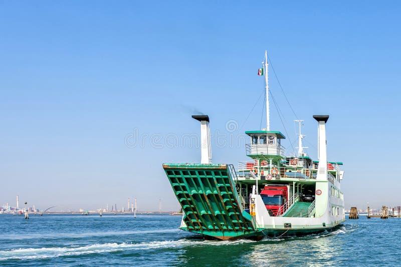 La vista di luce del giorno a verde ha caricato il traghetto che gira sull'acqua con la traccia immagini stock