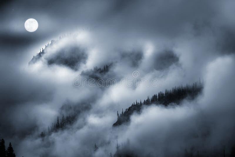 La vista di notte di nebbia ha coperto la montagna accesa dalla luna piena immagine stock