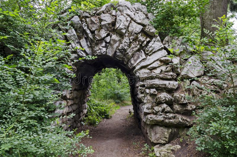 La vista di vecchio rockery abbandonato e la pietra incurvano brushy con la varia pianta nel vecchio parco ad ovest naturale fotografia stock