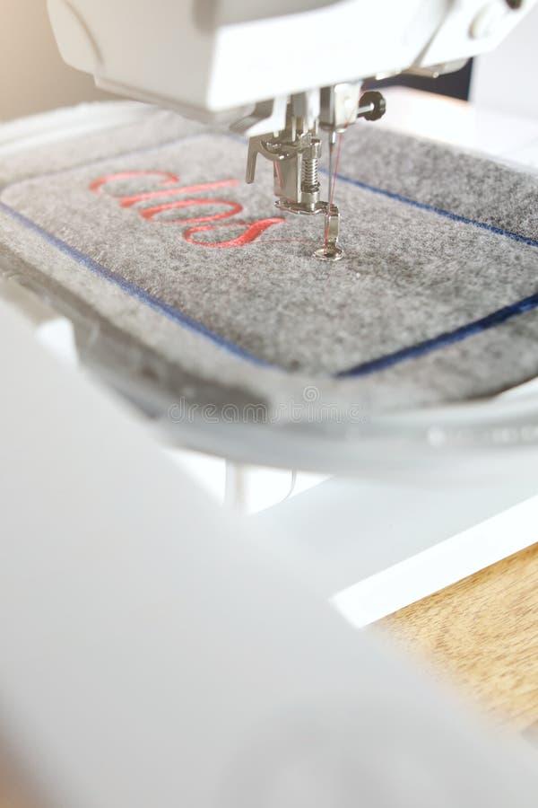 la vista diagonale su un'unità automatizzata del ricamo e della macchina per cucire che cuce l'iscrizione rossa sul grey ha riten immagini stock libere da diritti