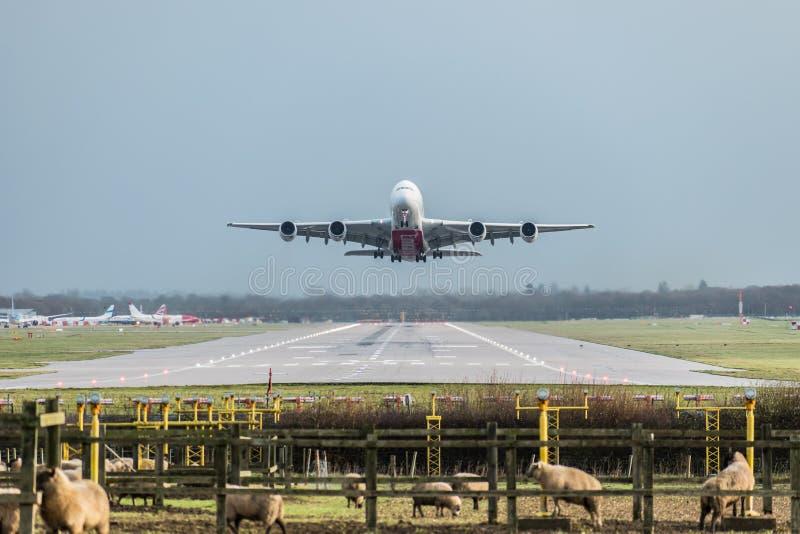 La vista direttamente giù la pista come aereo di linea aerea degli emirati decolla dall'aeroporto di Londra Gatwick che si dirige fotografia stock libera da diritti