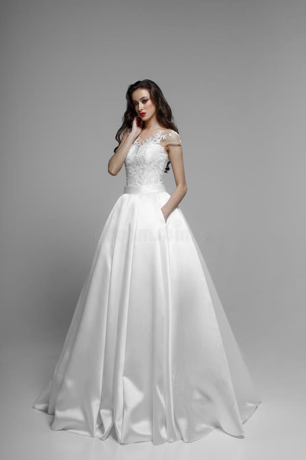 La vista frontal de un modelo moreno en vestido wendding, plantea la oferta en el estudio, aislado en un fondo blanco foto de archivo