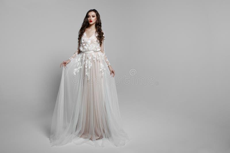 La vista horizontal de un modelo femenino hermoso con el pelo largo, compone en el vestido wendding, aislado en un fondo blanco imagen de archivo