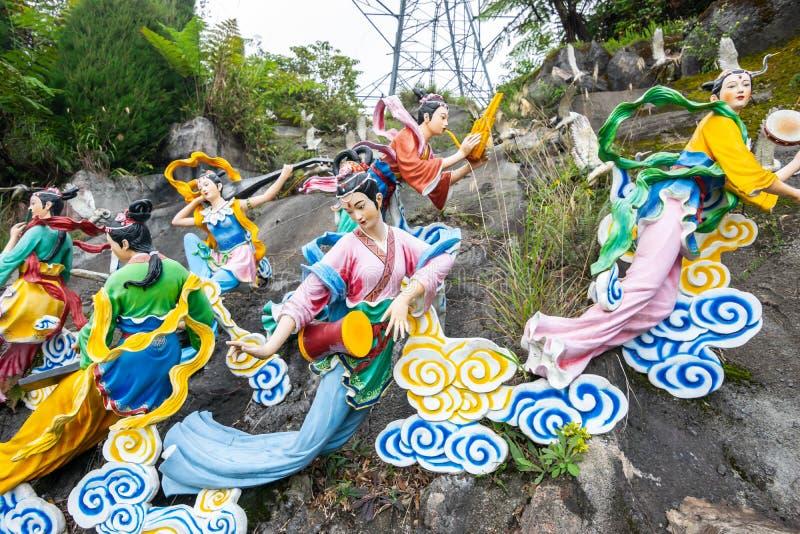 La vista icónica de estatuas de hadas en las nubes y el carro de la tracción con el ángel chino divino en Chin Swee Caves Temple imagenes de archivo