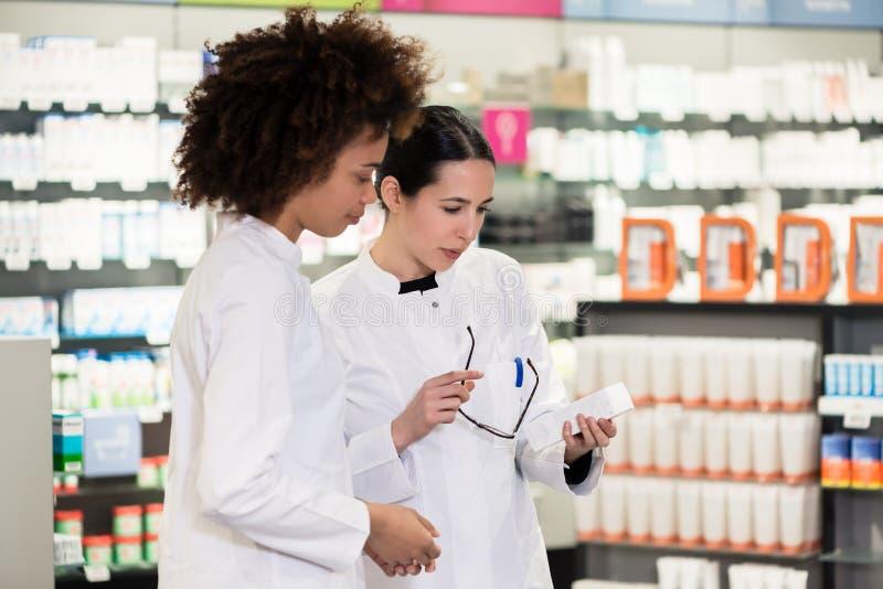 La vista lateral de dos dedicó a farmacéuticos en una farmacia contemporánea imagen de archivo libre de regalías