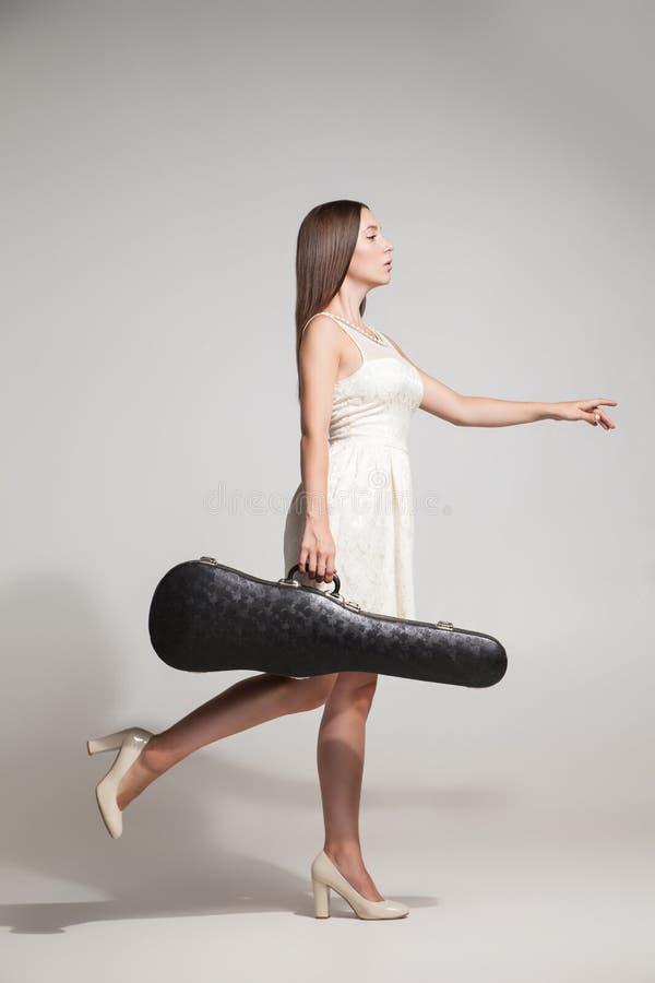 La vista lateral de la morenita en el vestido blanco lleva el violín en caso de que imagen de archivo libre de regalías