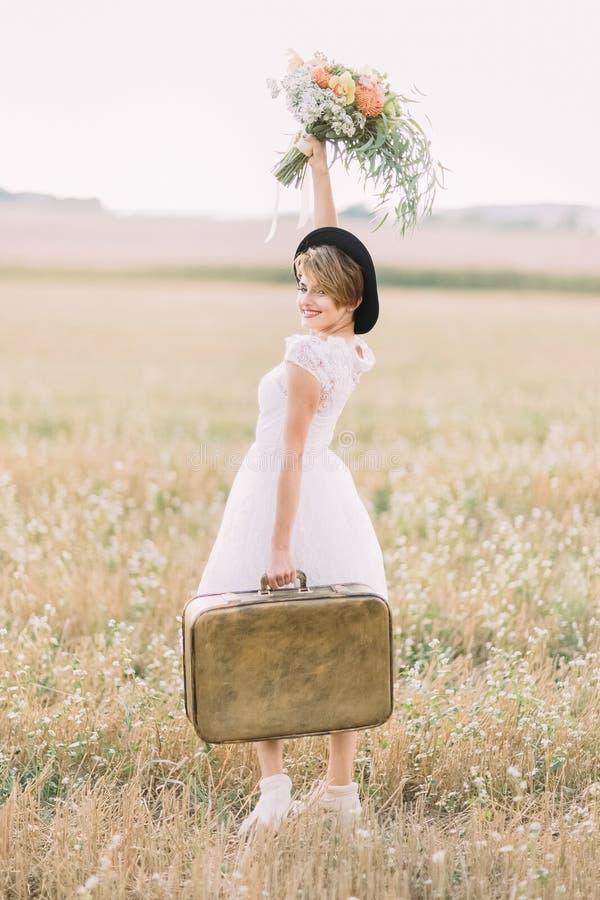 La vista lateral de la novia sonriente que lleva la maleta del vintage, continuando el ramo colorido y mirándolo imágenes de archivo libres de regalías