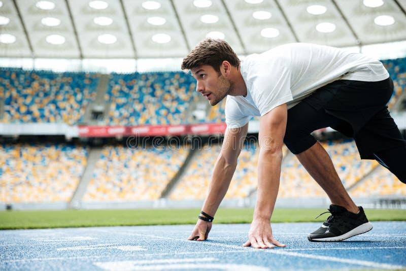 La vista lateral de un corredor masculino listo para los deportes ejercita imagen de archivo libre de regalías