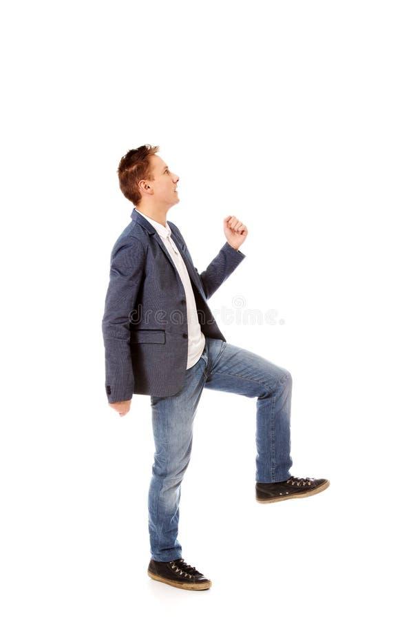 La vista lateral de un hombre de negocios sube las escaleras fotografía de archivo