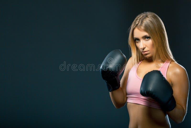 La vista lateral de una mujer joven magnífica en top sin mangas rosado está llevando guantes y la situación de boxeo grandes en f fotos de archivo