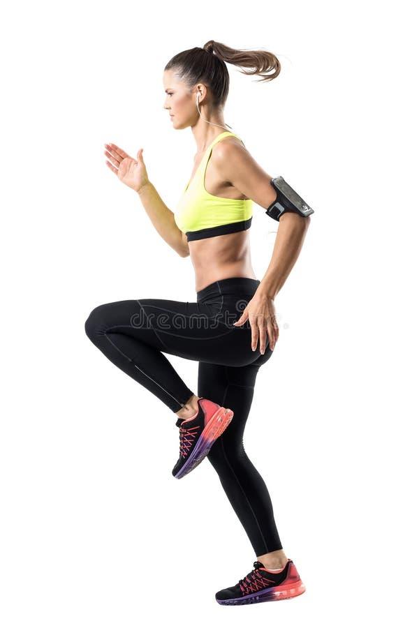 La vista lateral del movimiento parado de jóvenes enfocó al corredor femenino que esprintaba rápidamente anticipar imagen de archivo libre de regalías