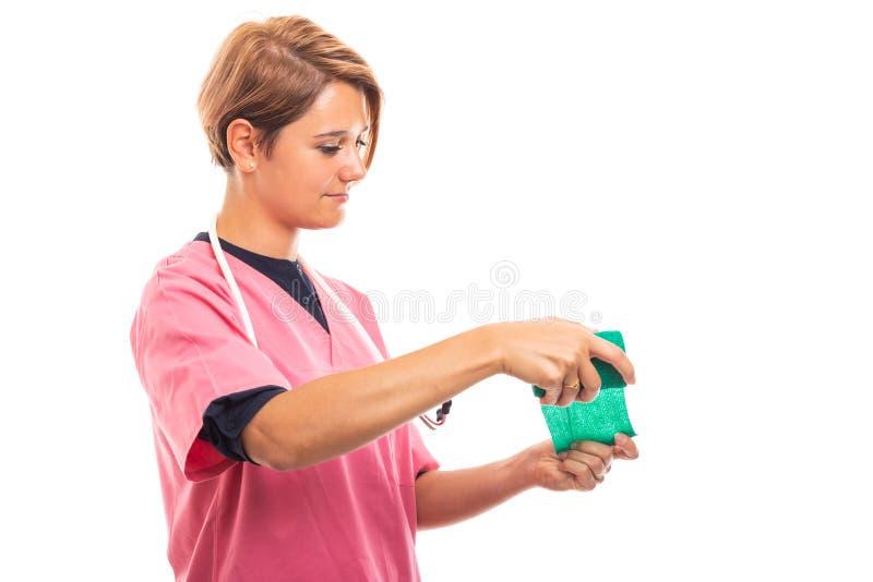 La vista lateral del rosa que lleva del veterinario de sexo femenino friega usando el vendaje verde imagen de archivo