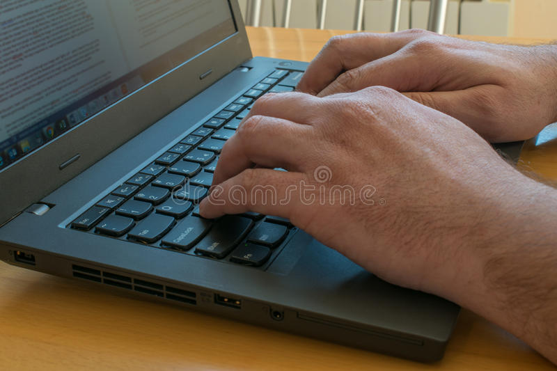 La vista lateral sobre el ordenador portátil en el escritorio con las manos masculinas se cierra para arriba imagenes de archivo