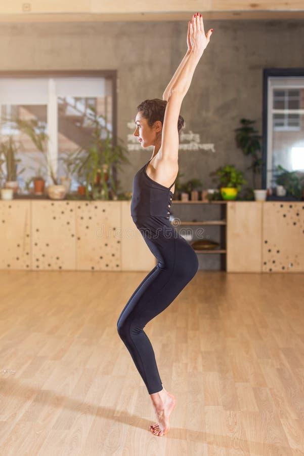 La vista laterale della donna che sta con le sue mani ha sollevato sulla preparazione per l'esercizio di yoga in una palestra immagine stock libera da diritti