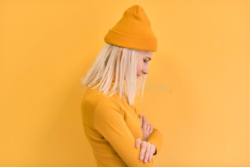 La vista laterale della donna graziosa dei capelli biondi indossa i vestiti gialli, cappello, posante sul fondo giallo dello stud immagine stock libera da diritti