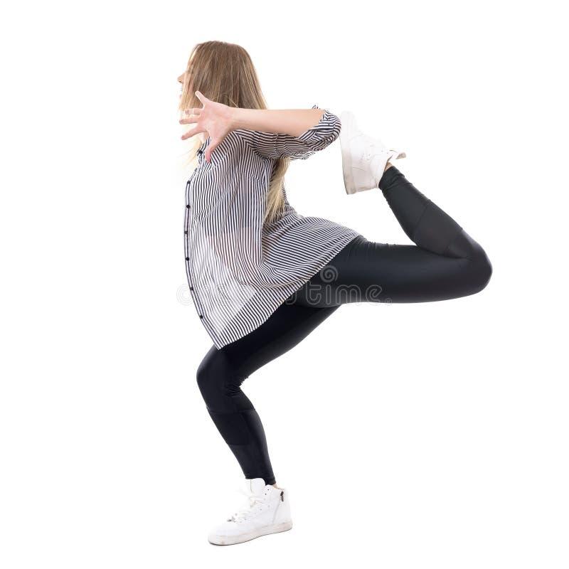 La vista laterale della prestazione femminile flessibile del ballerino di jazz su una gamba con l'altra gamba si è alzata dietro fotografia stock libera da diritti