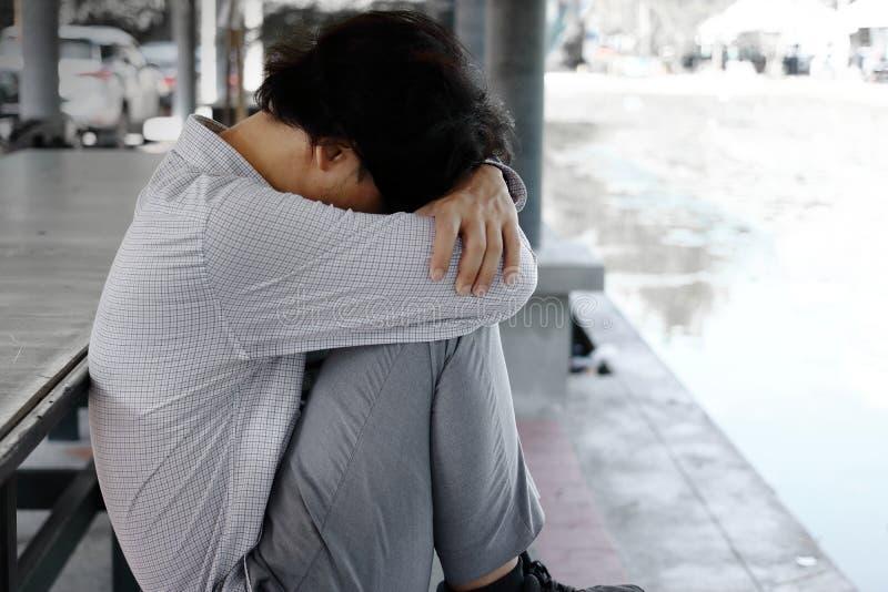 La vista laterale di giovane uomo asiatico esaurito frustrato di affari si siede ed abbraccia le sue ginocchia fino al petto fotografie stock
