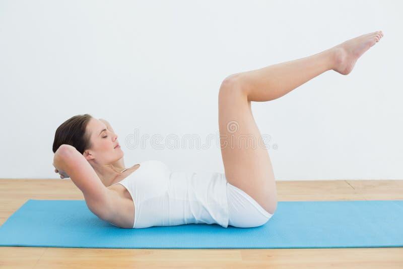 La vista laterale di una donna che fa lo stomaco sgranocchia sulla stuoia di esercizio fotografie stock