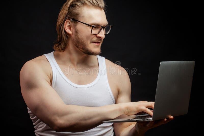 La vista laterale ha sparato di giovane sportivo che lavora nel computer portatile immagini stock libere da diritti