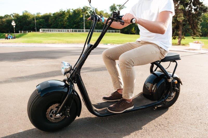 La vista laterale potata del giovane guida sulla motocicletta moderna fotografia stock