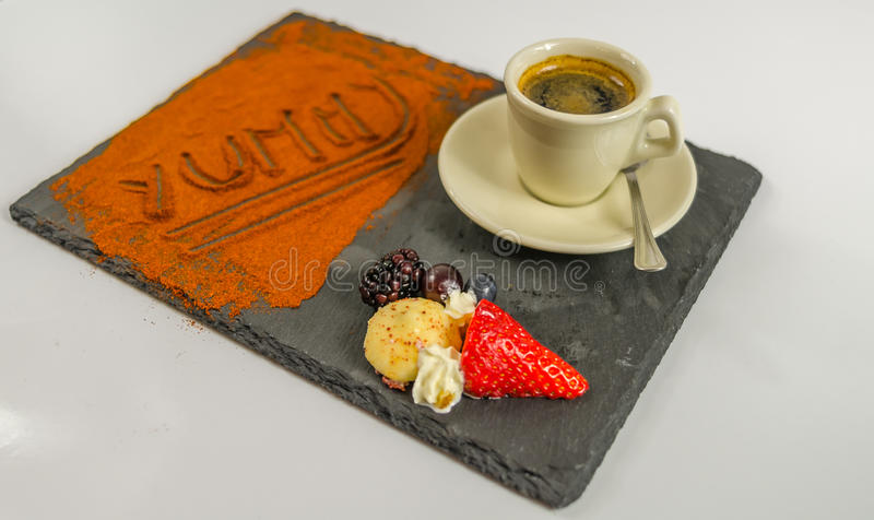 La vista laterale su caffè in una tazza fruttifica e la parola squisita sul nero fotografia stock libera da diritti