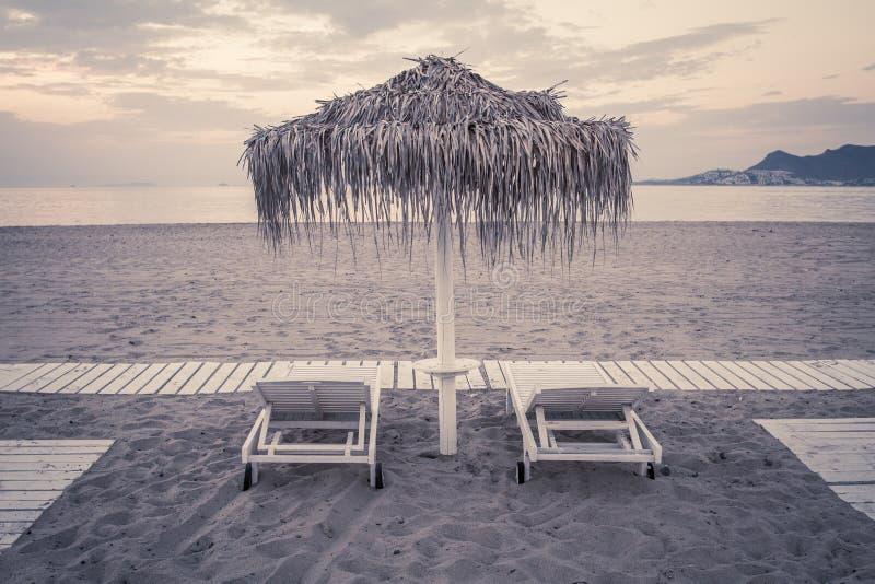 La vista lunatica del mare e della spiaggia con i parasoli a colore del chillout del tramonto ha spaccato la tonalità fotografia stock